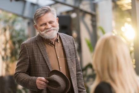 selective focus of smiling senior man with hat looking at woman at table in restaurant