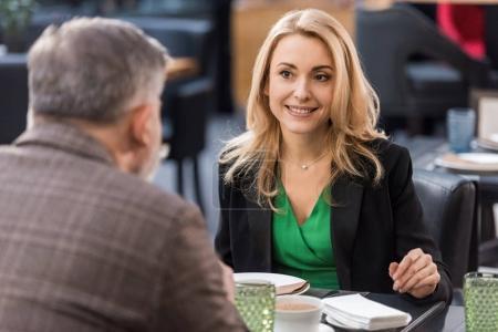 Photo pour Vue partielle de l'homme et la femme souriante en train de dîner ensemble au restaurant - image libre de droit