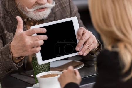 Photo pour Recadrée tir d'homme d'affaires senior avec tablette ayant rencontre d'affaires avec une collègue au café - image libre de droit