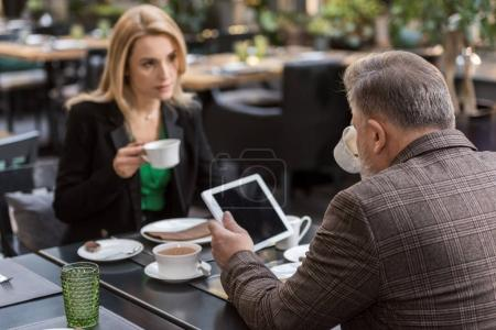 selective focus of business colleagues on business meeting in cafe