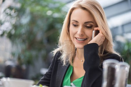 portrait of smiling businesswoman talking on smartphone