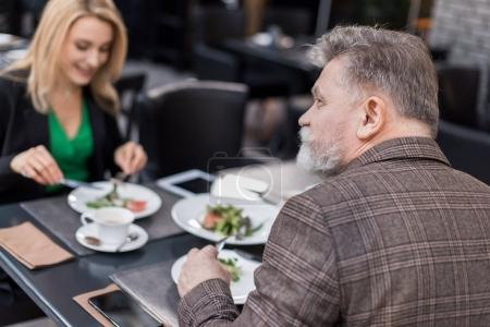 selective focus of senior man on romantic date with girlfriend in cafe