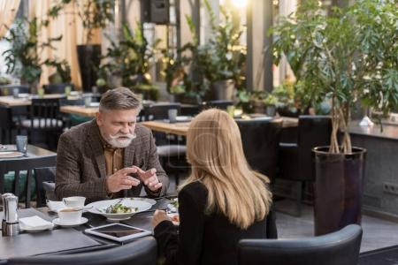 Photo pour Vue partielle du senior homme et femme en train de dîner ensemble au restaurant - image libre de droit