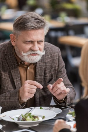 partial view of senior man and woman having dinner together in restaurant