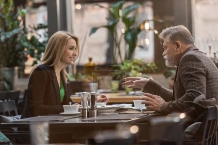 Photo pour Vue latérale du couple en train de dîner sur rendez-vous romantique au café - image libre de droit