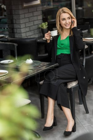 smiling woman with cup of coffee talking on smartphone in cafe