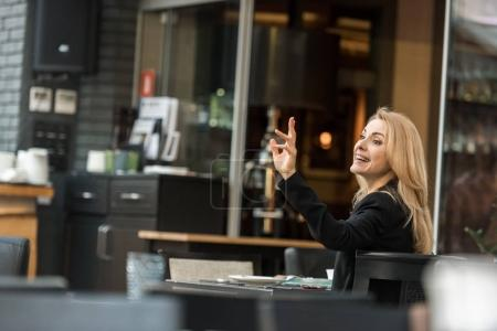 side view of smiling woman calling for waiter in restaurant