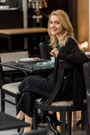 beautiful smiling woman looking at camera while sitting at table in cafe