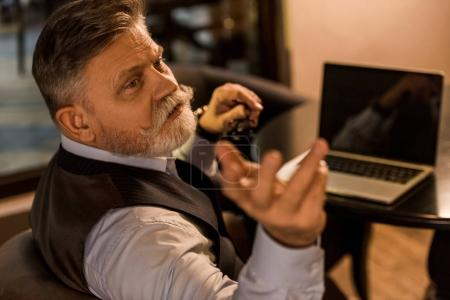 senior bearded businessman calling for waiter in cafe