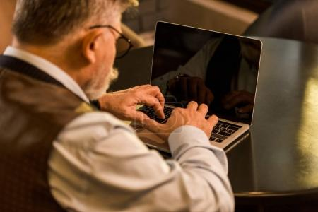 selective focus of senior businessman typing on laptop in cafe