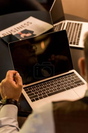 cropped shot of businessman sitting at table with laptop in cafe