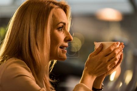 side view of beautiful woman with cup of coffee in hands