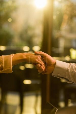 partial view of man and woman holding hands in cafe