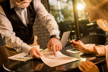 partial view of business partner signing contract at business meeting in cafe