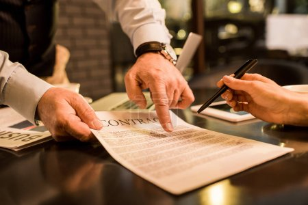 Photo pour Recadrée tir de femme d'affaires, signature du contrat au cours de la réunion avec business collègue au café - image libre de droit