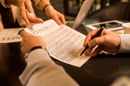 businessman signing contract during meeting with business colleague in cafe