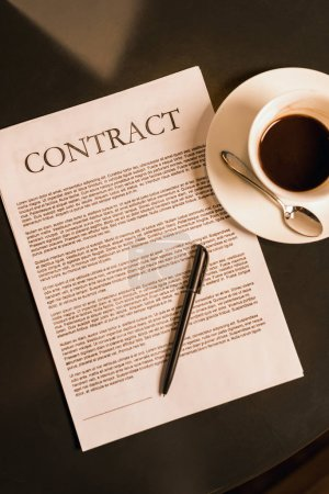 top view of contract and cup of coffee on dark tabletop