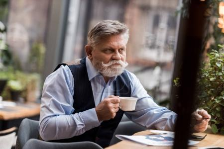 portrait of senior bearded man with cup of coffee sitting a table in cafe