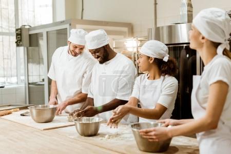 Photo pour Groupe de boulangers multiethniques heureux pétrissant la pâte ensemble - image libre de droit