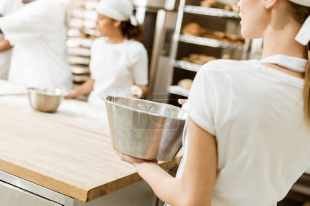 female baker with bowl of ingredients for pastry at baking manufacture