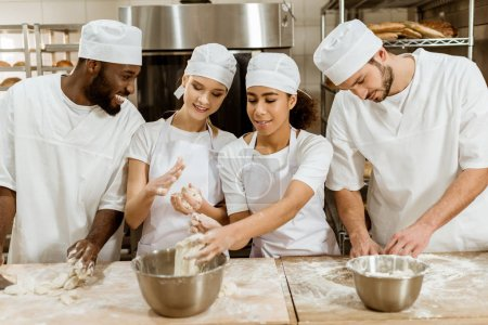 group of young baking manufacture workers kneading dough together