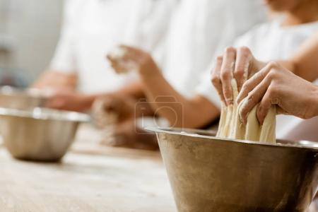 Photo for Cropped shot of baking manufacture workers kneading dough together - Royalty Free Image