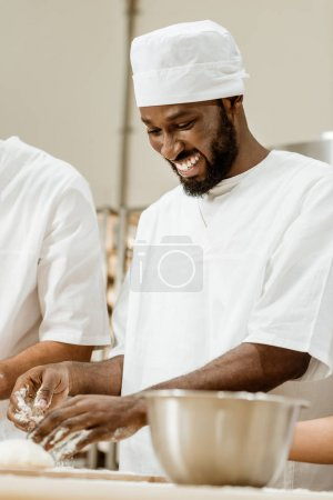 handsome african american baker kneading dough for pastry at baking manufacture