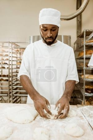 handsome african american baker preparing raw dough for pastry on baking manufacture