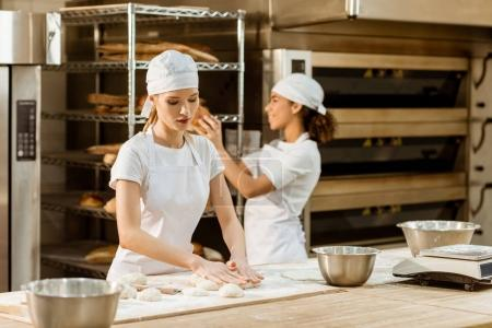 young attractive female bakers working together at baking manufacture