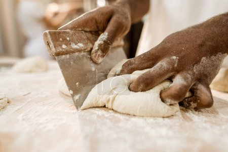 Photo for Cropped shot of baker cutting raw dough with dough knife - Royalty Free Image
