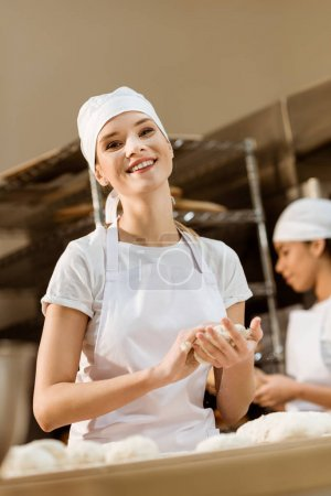 happy female baker kneading dough at baking manufacture while her colleague working blurred on background