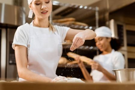 happy female baker kneading dough and pouring flour on it at baking manufacture while her colleague working blurred on background