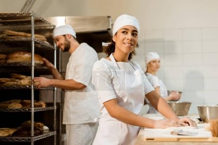 Photo for Happy female baker working at baking manufacture - Royalty Free Image