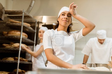 happy and tired female baker working at baking manufacture