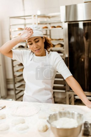 overworked female baker wiping sweat from forehead at baking manufacture