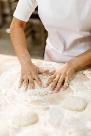 Photo for Cropped shot of female baker kneading dough for pastry on messy table - Royalty Free Image