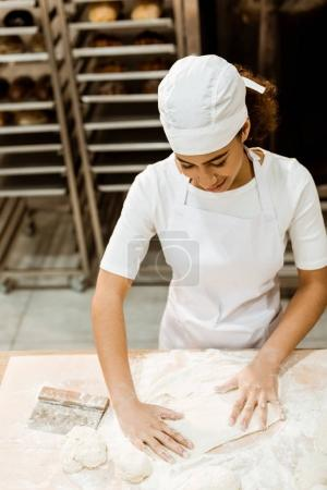 Photo for High angle view of female baker preparing dough for pastry on baking manufacture - Royalty Free Image