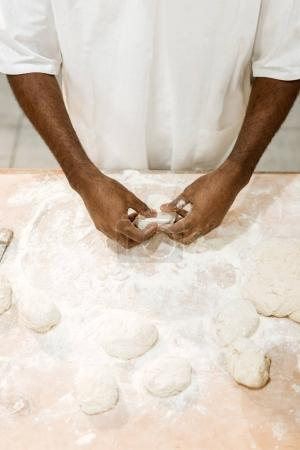 cropped shot of african american baker preparing dough for pastry