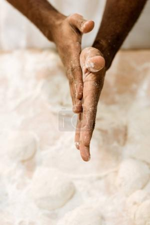 cropped shot of african american baker preparing dough for pastry and covering hands in flour