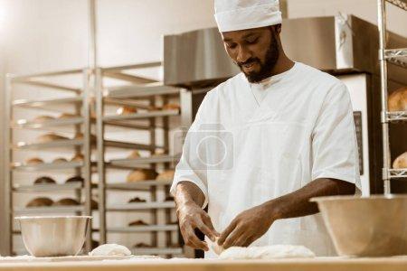 Photo pour Beau boulanger afro-américain préparant la pâte sur la fabrication de cuisson - image libre de droit