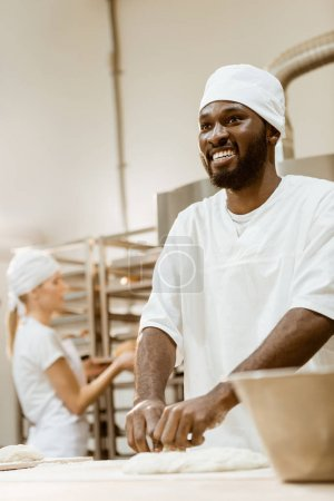 happy african american baker kneading dough while his female colleague working on background at baking manufacture