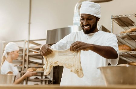happy handsome african american baker preparing dough on baking manufacture