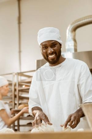 handsome african american baker kneading dough on baking manufacture