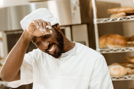 overworked african american baker wiping sweat on baking manufacture