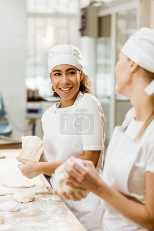 happy female bakers kneading dough together at baking manufacture