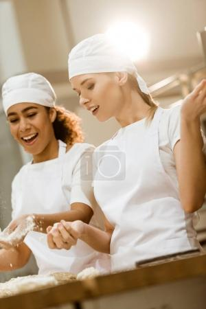 attractive female bakers kneading dough together at baking manufacture