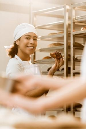 beautiful female baker with delicious croissant on baking manufacture