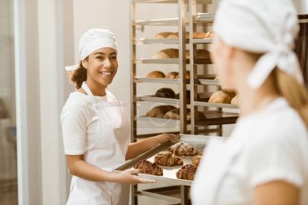 Photo pour Female boulangers travaillent ensemble de cuisson fabriquent abd parler - image libre de droit
