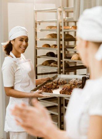 Photo pour Jeunes boulangeries féminines travaillant ensemble à la fabrication de boulangerie parler abd - image libre de droit