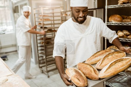 Photo for Handsome african american baker taking bread loaves from oven at baking manufacture - Royalty Free Image